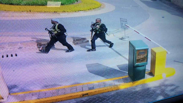 """In this grab taken from security camera footage released to the local media, heavily armed attackers walk in the compound of a hotel, in Nairobi, Kenya, Tuesday, Jan. 15, 2019. Extremists launched an attack on a luxury hotel in Kenya's capital, sending people fleeing in panic as explosions and heavy gunfire reverberate through the neighborhood. A police officer says he saw bodies, """"but there was no time to count the dead."""" Al-Shabab _ the Somalia-based extremist group _ is claiming responsibility. (Security Camera Footage via AP)"""