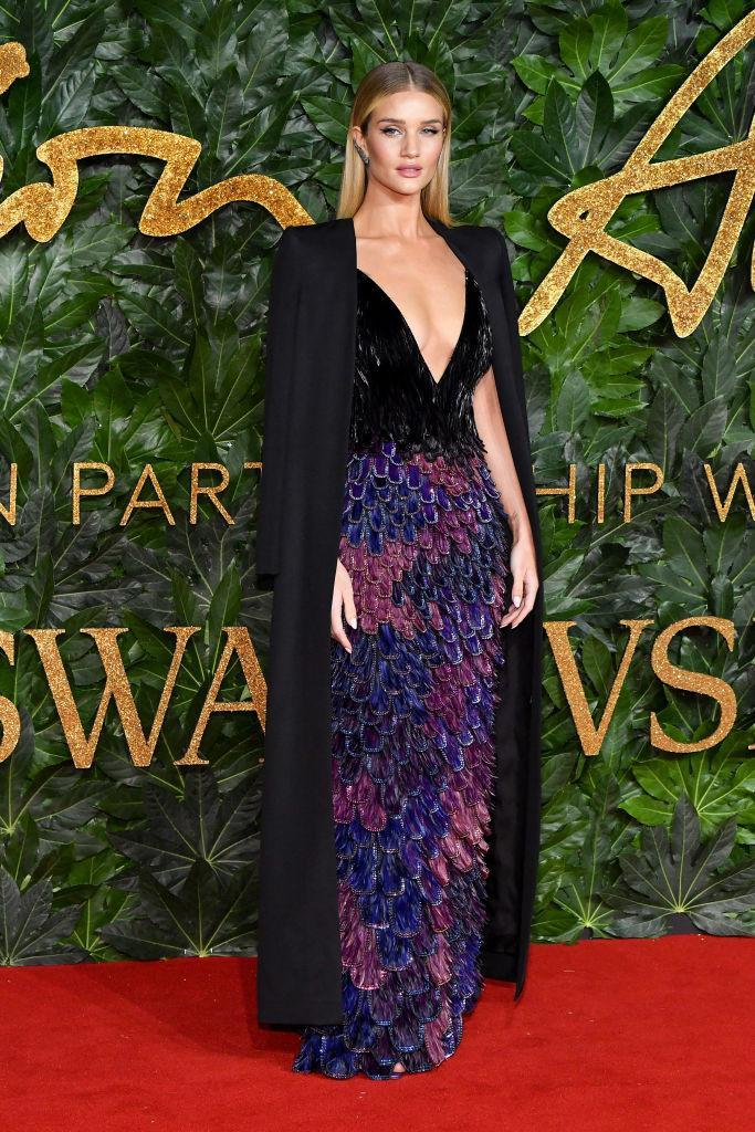 <p>Rosie Huntington-Whiteley wore a sequinned dress by Givenchy on the red carpet with a coat draped over her shoulders. <em>[Photo: Getty]</em> </p>