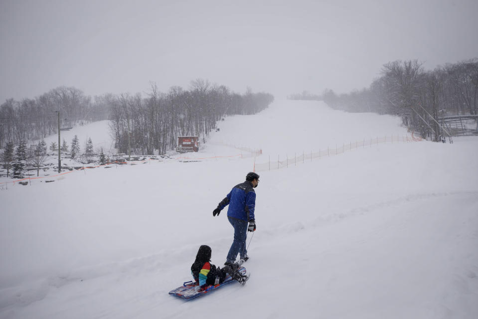 A man pulls a child in a sled by the shut-down slopes of Blue Mountain Ski Resort in The Blue Mountains, Ontario, on the first day of a provincial lockdown amid a 12-day trend of over 2,000 daily COVID-19 cases, Saturday, Dec. 26, 2020. (Cole Burston/The Canadian Press via AP)