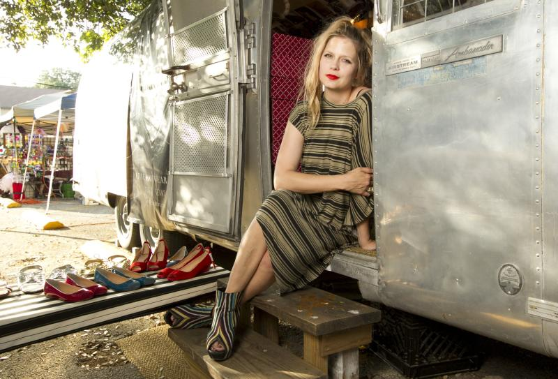 In this photo taken April 5, 2012, Sarah Ellison Lewis, the owner of Bootleg, a shoe trailer with hard-to-find footwear labels poses in Austin, Texas. When former fashion editor Sarah Ellison Lewis wanted to open an upscale, funky shoe boutique in Austin, Texas, she had sticker shock every time she saw the price for a store lease. She worried the hefty rent would limit her ability to turn a profit so she bought a 30-foot trailer, decorated it with vintage wallpaper photography and reclaimed wooden benches and signed a lease on a parking spot between a chic hotel and popular brunch spot in an eclectic neighborhood for a quarter of the cost of a traditional store. (AP Photo/Statesman.com, Jay Janner)  MANDATORY CREDIT: JAY JANNER/STATESMAN.COM