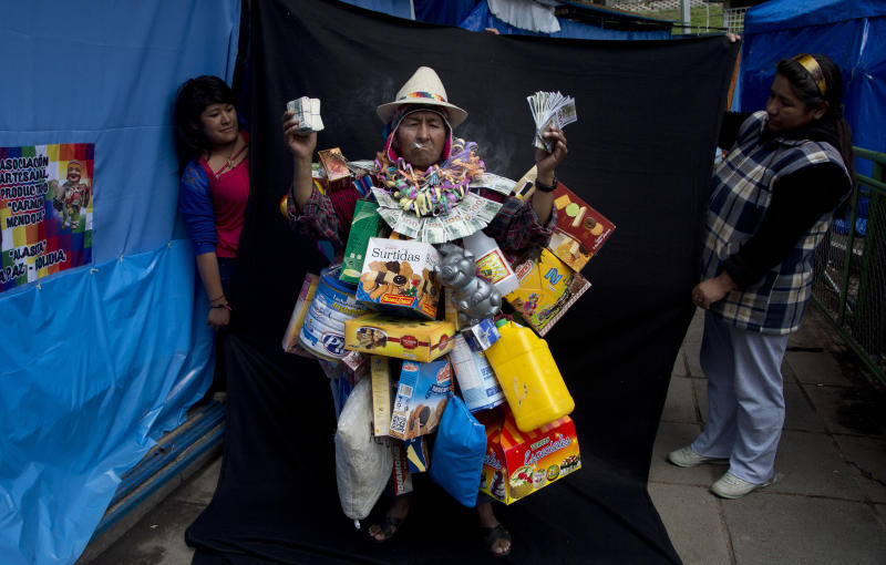 "In this Feb. 3, 2018 photo, fair vendors hold up a black backdrop behind Alberto Macias Rios, dressed as ""Ekeko,"" the god of prosperity and the central figure of the Alasita Fair, as he poses for a picture in La Paz, Bolivia. Macias, 65, says his low stature helps him pull off the Ekeko personality. ""I grew up with the Alasitas fair accompanying my mother when the fair filled various streets and avenues of La Paz,"" he said. Macias competed in this year's Ekeko costume competition. (AP Photo/Juan Karita)"