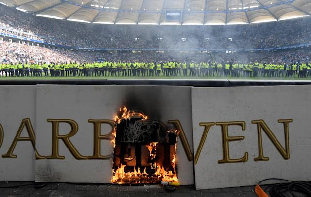 Soccer Football - Bundesliga - Hamburger SV v Borussia Moenchengladbach - Volksparkstadion, Hamburg, Germany - May 12, 2018 General view of an advertising board on fire as stewards are lined up across the pitch after the match is interrupted by fan trouble REUTERS/Fabian Bimmer DFL RULES TO LIMIT THE ONLINE USAGE DURING MATCH TIME TO 15 PICTURES PER GAME. IMAGE SEQUENCES TO SIMULATE VIDEO IS NOT ALLOWED AT ANY TIME. FOR FURTHER QUERIES PLEASE CONTACT DFL DIRECTLY AT + 49 69 650050 TPX IMAGES OF THE DAY