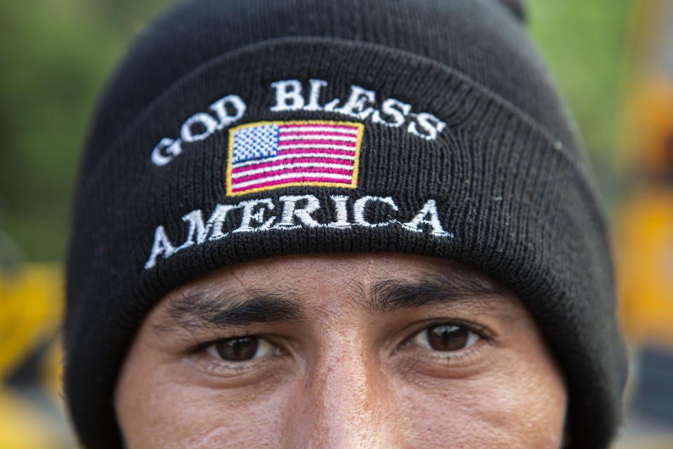 An Honduran migrant who tried to the U.S.-Mexico border eyes the camera wearing a God Bless America beanie, after he was detained and returned to his home country, in Copan, Honduras, Wednesday, Jan. 20, 2021. After a year of pandemic-induced paralysis, those in daily contact with migrants believe the flow north could return to the high levels seen in late 2018 and early 2019. (AP Photo/Oliver de Ros)