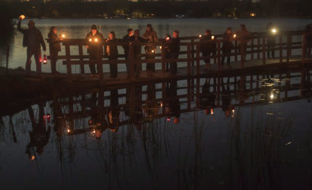 Fans of the Tragically Hip gather for a candlelight vigil by the water's edge in Bobcaygeon, Ont. to pay tribute to singer Gord Downie.
