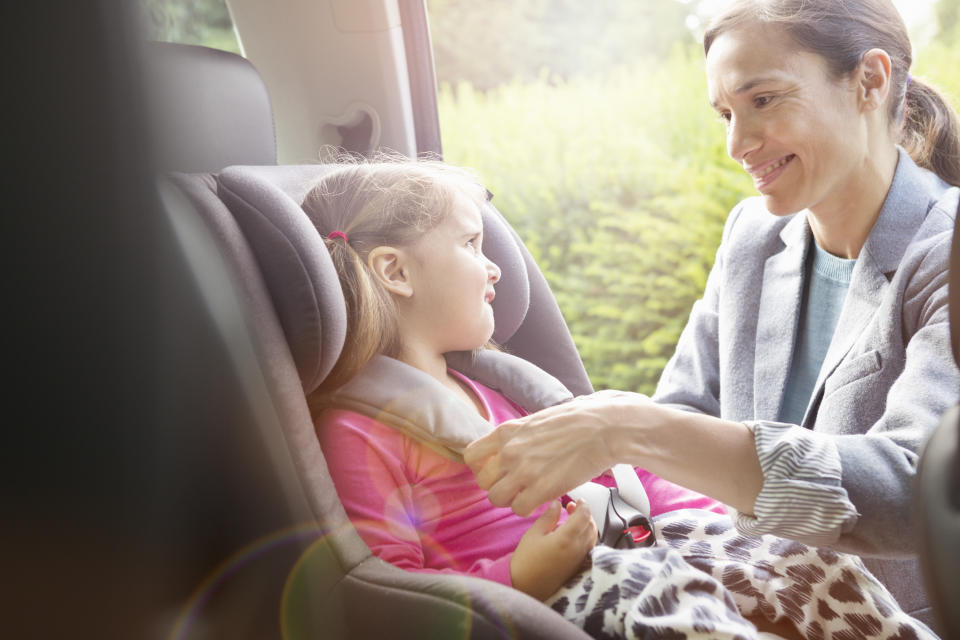 Mum strapping daughter in car seat. Source: Getty Images