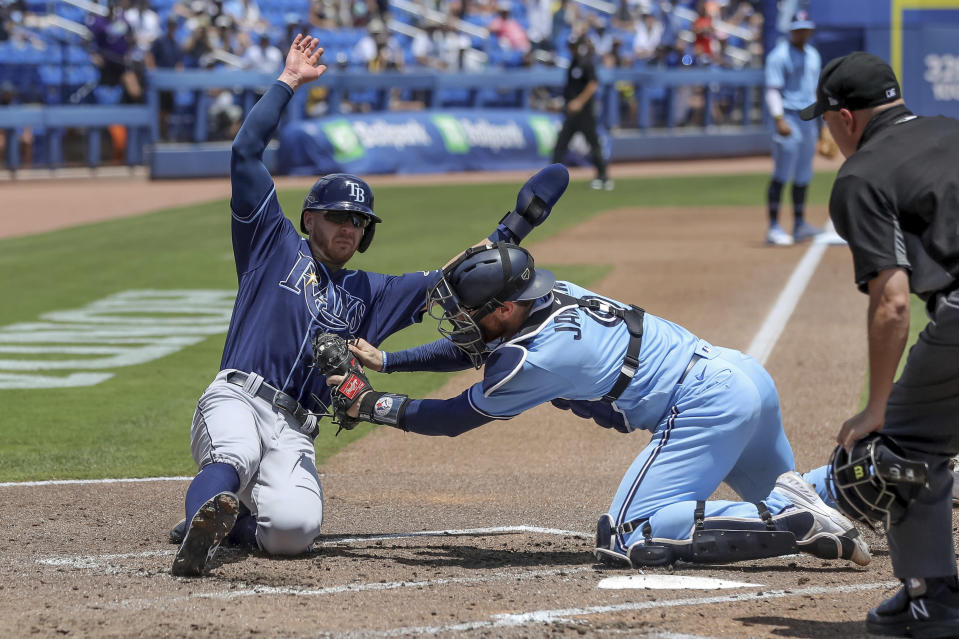 Toronto Blue Jays catcher Danny Jansen tags out Tampa Bay Rays' Mike Brosseau as home plate umpire Jansen Visconti watches during the fourth inning of a baseball game Sunday, May 23, 2021, in Dunedin, Fla. (AP Photo/Mike Carlson)