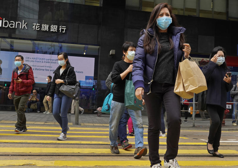 In this Monday, Feb. 3, 2020, photo, people wear masks walking in a downtown street in Hong Kong. Hong Kong on Tuesday reported its first death from a new virus, a man who had traveled from the mainland city of Wuhan that has been the epicenter of the outbreak. (AP Photo/Vincent Yu)