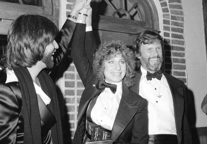 """FILE - In this Dec. 23, 1976 file photo, producer Jon Peters, from left, Barbra Streisand and Kris Kristofferson appear at a preview of the film, """"A Star is Born,"""" in New York. Streisand is giving an early thumbs-up to the remake of """"A Star Is Born"""" with Lady Gaga and Bradley Cooper. Streisand and Kristofferson topped the 1976 version of the romantic drama about a rising performer and a fading star. (AP Photo/Suzanne Vlamis, File)"""