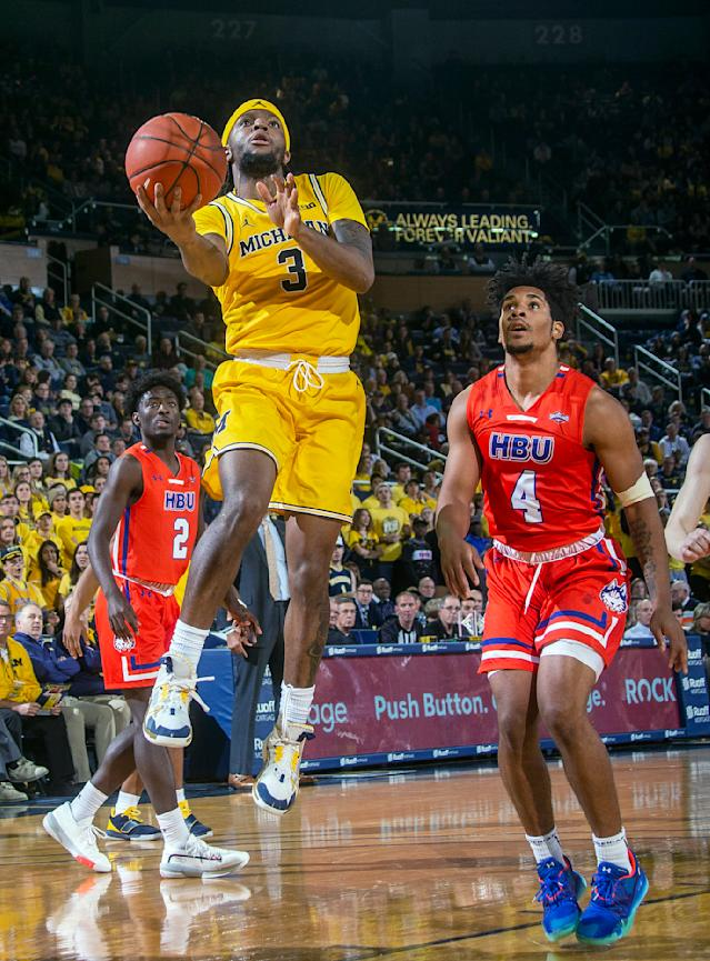 Michigan guard Zavier Simpson (3) shoots as Houston Baptist guard Myles Pierre (4) defends during the second half of an NCAA college basketball game in Ann Arbor, Mich., Friday, Nov. 22, 2019. Michigan won 111-68. (AP Photo/Tony Ding)