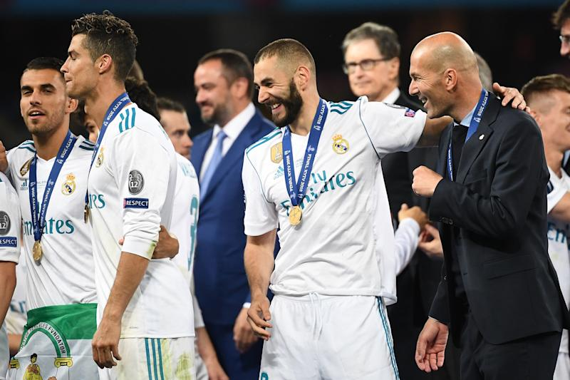 Real Madrid's French coach Zinedine Zidane (R), Real Madrid's French forward Karim Benzema (C) and Real Madrid's Portuguese forward Cristiano Ronaldo (L) celebrate after winning the UEFA Champions League final football match between Liverpool and Real Madrid at the Olympic Stadium in Kiev, Ukraine, on May 26, 2018. (Photo by FRANCK FIFE / AFP) (Photo credit should read FRANCK FIFE/AFP via Getty Images)