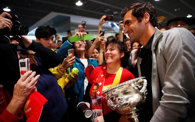 Switzerland's Roger Federer holds his Australian Open trophy as he poses for pictures with fans upon his arrival at Zurich Airport, Switzerland January 30, 2018. REUTERS/Arnd Wiegmann -