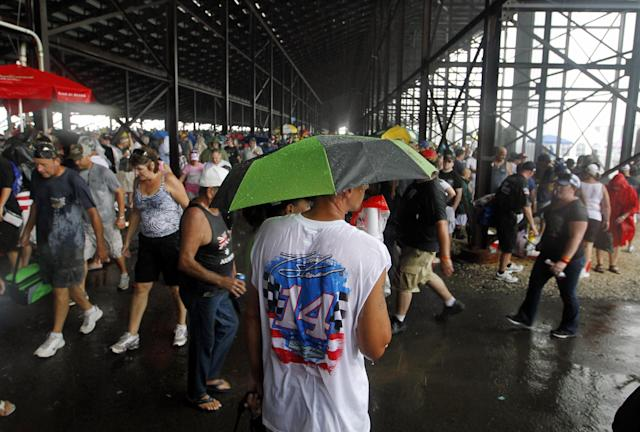 Fans stand under the grandstand after the start of the NASCAR Sprint Cup Series auto race was postponed due to rain on Sunday, Aug. 5, 2012, at Pocono Raceway in Long Pond, Pa. (AP Photo/Mel Evans)