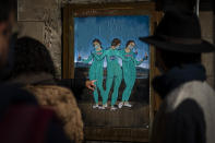 """People look at a painting by Italian street artist TvBoy named """"The three Vaccines"""" depicting The Three Graces by Italian painter Raphael in Barcelona, Spain, Friday, Jan. 22, 2021. Although health authorities believe that the surge of coronavirus infections is waning, the rate of contagion has shot to over three times the extreme risk level, dangerously straining the health system. (AP Photo/Emilio Morenatti)"""