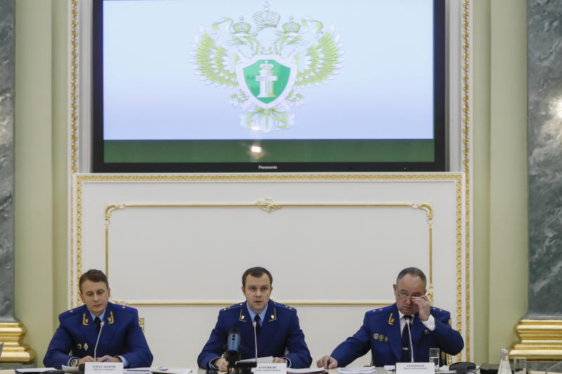 """From left, an aide to the Russian Prosecutor General Mikhail Alexandrov, Russian Prosecutor General spokesman Alexander Kurennoi, and an aide to the Russian Prosecutor General Nikolai Atmoniev attend a news conference in Moscow, Russia, Monday, Nov. 19, 2018. Russian prosecutors on Monday announced new charges against Bill Browder, accusing him of forming a criminal group to embezzle funds in Russia. They also said they suspect Magnitsky's death in prison was a poisoning and said they have a """"theory"""" Browder is behind the poisoning. (AP Photo/Pavel Golovkin)"""