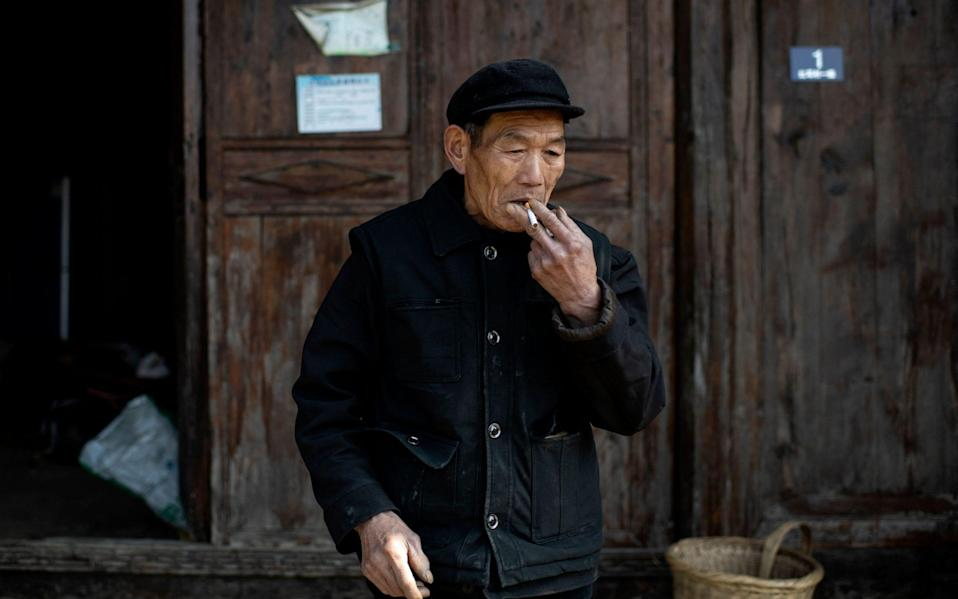 """This picture taken on January 13, 2021 shows farmer Mi Jiazhi smoking in front of his old residence in Baojing county, in central China's Hunan province. - China's decades-long war to eradicate extreme poverty has yielded remarkable results, with Chinese President Xi Jinping declaring the target was reached in 2020 heralding a """"major victory"""". But reality on the ground is patchier, with experts warning that rising incomes have made China's poverty line outdated. - Noel Celis/AFP"""