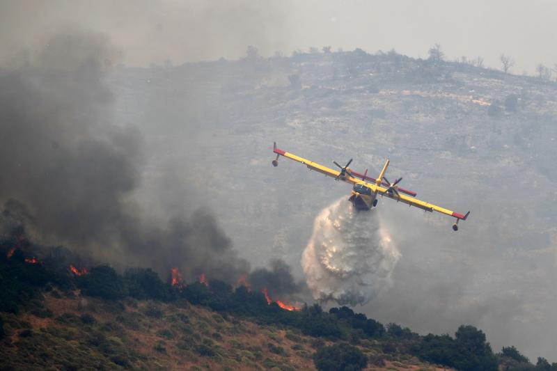 An airplane drops water over a fire in the village of Gavalas, on the Greek island of Evia, Friday, July 5, 2019. Greek authorities say four villages were evacuated overnight on the island of Evia after two new brush fires broke out several hours after a major blaze led to the mobilization of more than 100 firefighters and the evacuation of another village. (AP Photo/Thanassis Stavrakis)