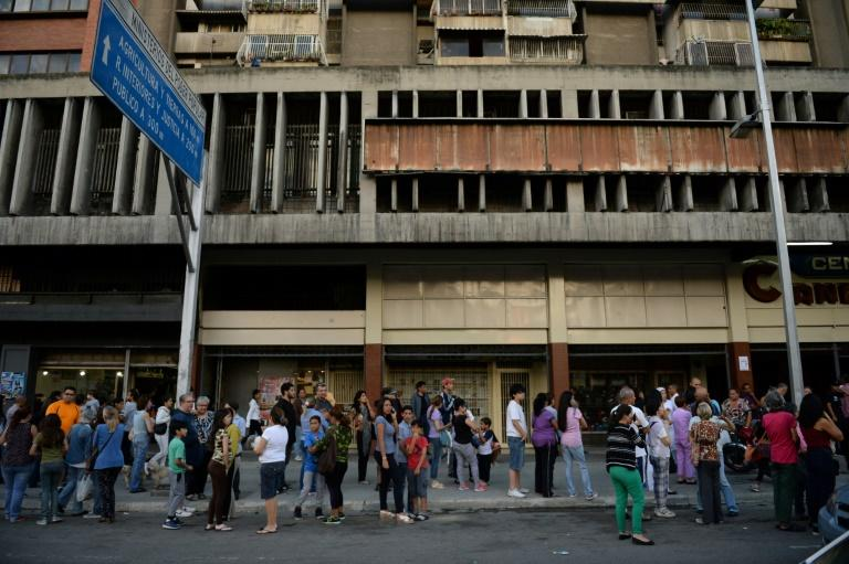 People wait in the streets after evacuating buildings in Caracas