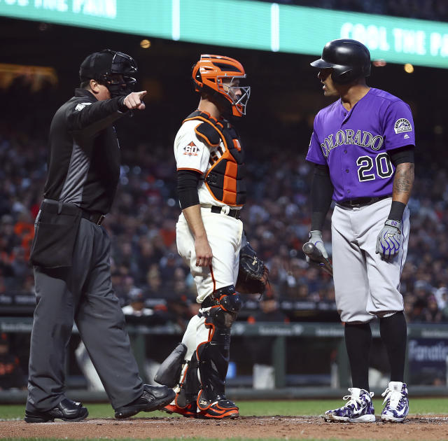 Home plate umpire Mike DiMuro, left, points to the dugout as Colorado Rockies Ian Desmond (20) argues a called third strike during the fifth inning of a baseball game against the San Francisco Giants on Wednesday, June 27, 2018, in San Francisco. Giants catcher Buster Posey is at center. (AP Photo/Ben Margot)