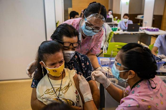 Parents hold onto their children as they receive their first dose of the Pfizer Covid-19 vaccine at Vachira Hospital on September 21, 2021 in Bangkok, Thailand.