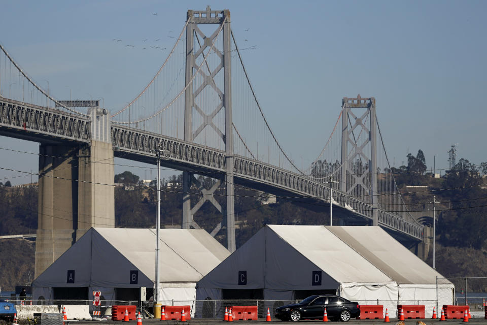 Tents from a COVID-19 testing site sit in front of the San Francisco-Oakland Bay Bridge during the coronavirus outbreak in San Francisco, Monday, Nov. 16, 2020. (AP Photo/Jeff Chiu)