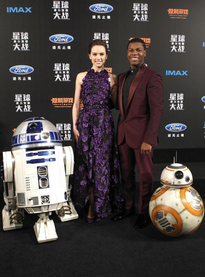 <p>For the Shanhai premiere of <i>Star Wars: The Force Awakens, </i>the film's young actors showed off their considerable fashion skills. Daisy Ridley, who's been on a sartorial roll wearing designer pieces around the world, wore a beautiful purple gown with matching shoes from Jason Wu. Her co-star, John Boyega, opted for a Versace suit in the same color family.R2D2 and BB-8 simply wiped off some dust for the special occasion. <i>Photo: Corbis</i><br /></p>