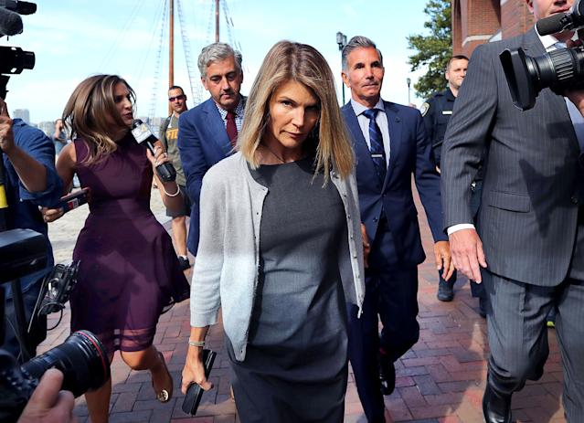 Lori Loughlin, center, and her husband Mossimo Giannulli, behind her at right, leave the John Joseph Moakley United States Courthouse in Boston on Aug. 27, 2019. (Photo by John Tlumacki/The Boston Globe via Getty Images)