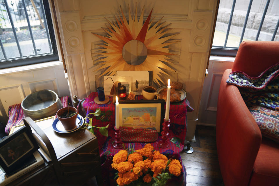 "A Day of the Dead altar decorated with photographs, candles, marigolds and favorite items and foods sits in Sebastian Diaz Aguirre's living room in the Brooklyn borough of New York, Wednesday, Oct. 28, 2020. ""It feels extremely comforting. I do feel I have a connection with my dad,"" said Diaz Aguirre, who set up the altar in remembrance of his father. (AP Photo/Emily Leshner)"