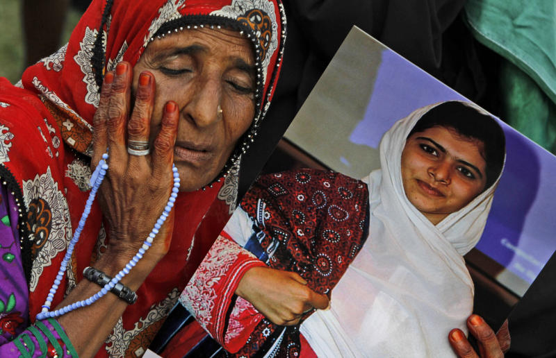 A supporter of Pakistani political party Muttahida Qaumi Movement (MQM), reacts while holding a poster of 14-year-old schoolgirl Malala Yousufzai, who was shot last Tuesday by the Taliban for speaking out in support of education for women, during a rally to condemn the attack in Karachi, Pakistan, Sunday, Oct. 14, 2012. Tens of thousands rallied in Pakistan's largest city Sunday in support of a 14-year-old girl who was shot and critically wounded by the Taliban for promoting girls' education and criticizing the militant group. (AP Photo/Shakil Adil)