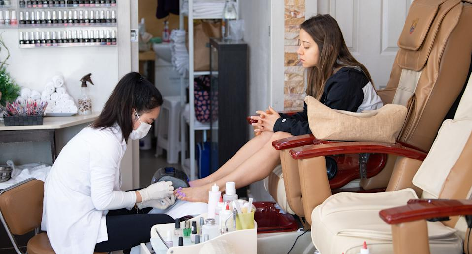 A woman getting a pedicure from a woman in a mask.