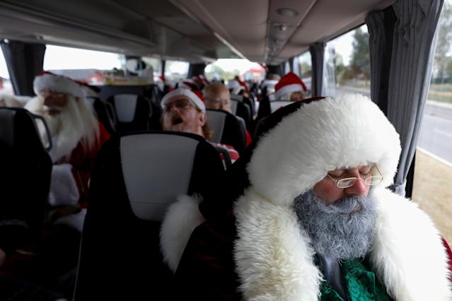 <p>People dressed as Santa Claus rest while on a bus trip between events during the World Santa Claus Congress, an annual event held every summer in Copenhagen, Denmark, July 23, 2018. (Photo: Andrew Kelly/Reuters) </p>