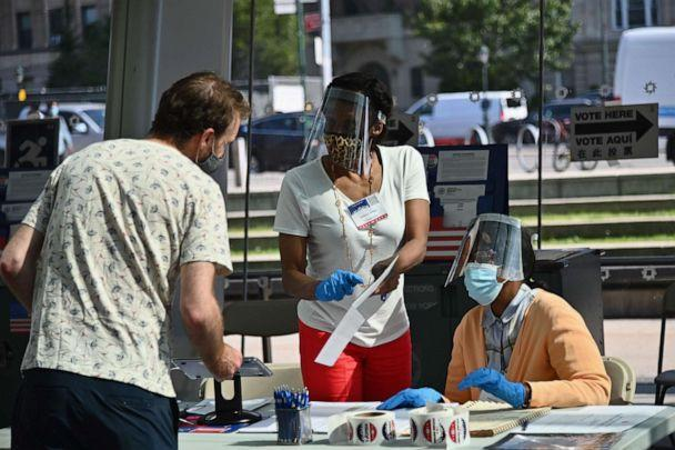 PHOTO: Board of Election employees and volunteers wearing PPE (personal protective equipment) assist voters at the Brooklyn Museum polling site for the New York Democratic presidential primary elections on June 23, 2020 in New York City. (Angela Weiss/AFP via Getty Images)