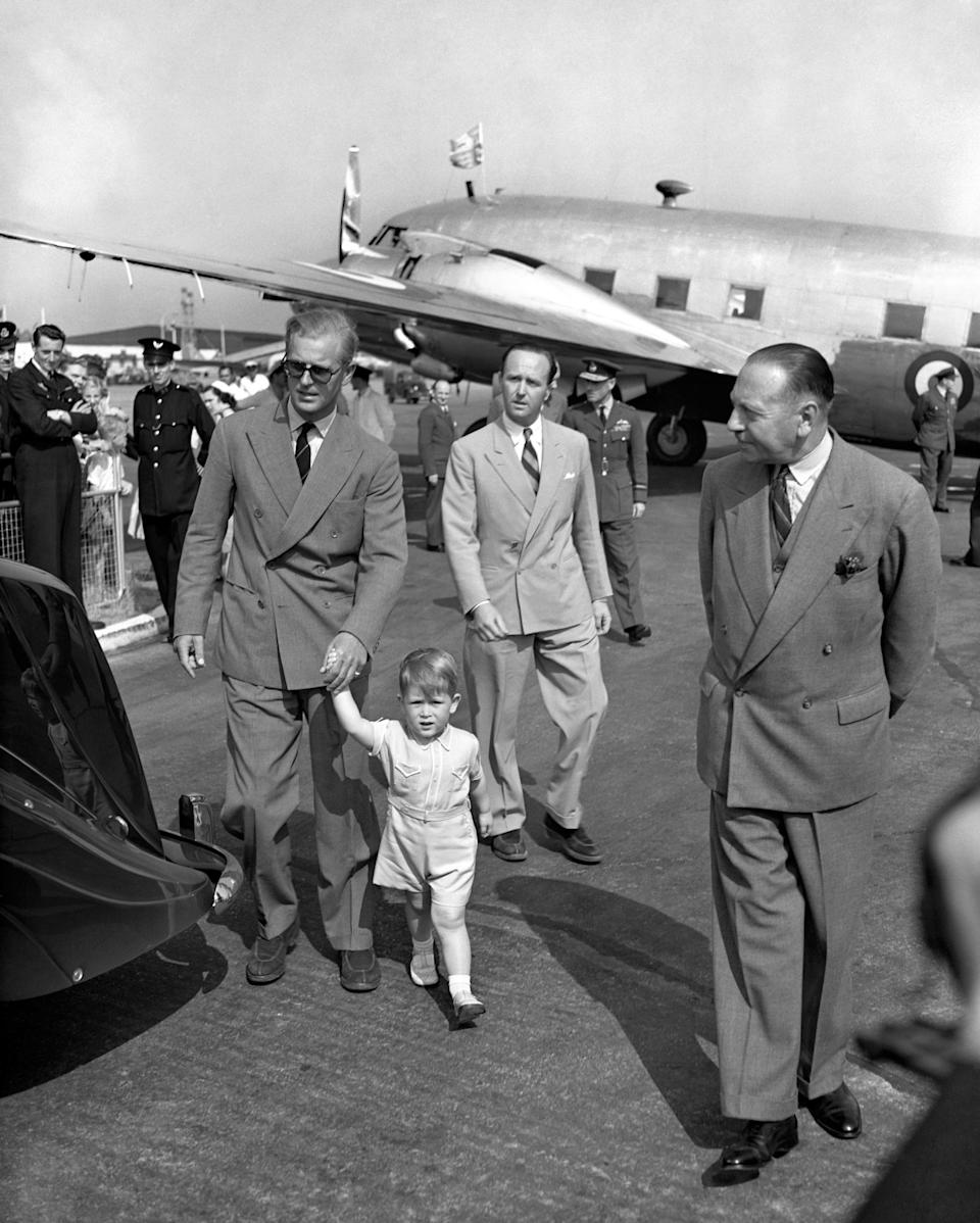 Prince Charles leading his father by the hand from the Viking Aircraft of the King's Flight in which the Duke of Edinburgh arrived home from Malta. The 2 year old Prince went to London airport to greet his father, while his mother, Princess Elizabeth, was at Ascot races to watch the Festival Stakes. The Duke has just handed over his command of the frigate, Magpie.   (Photo by PA Images via Getty Images)