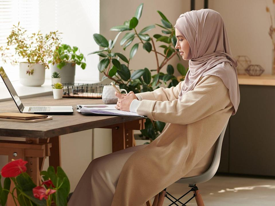 Young Muslim woman wearing headscarf sitting alone in cozy office room surfing Internet on smartphone during break, copy space