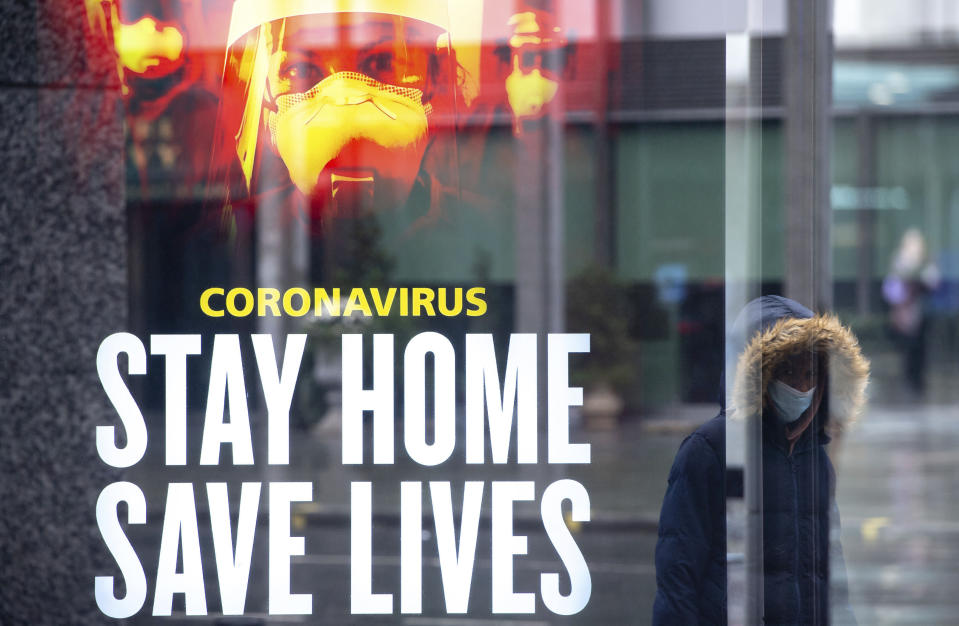 A woman passes a government conronavirus advert in central London, during England's third national lockdown to curb the spread of coronavirus, Thursday, Jan. 14, 2021. (Dominic Lipinski/PA via AP)