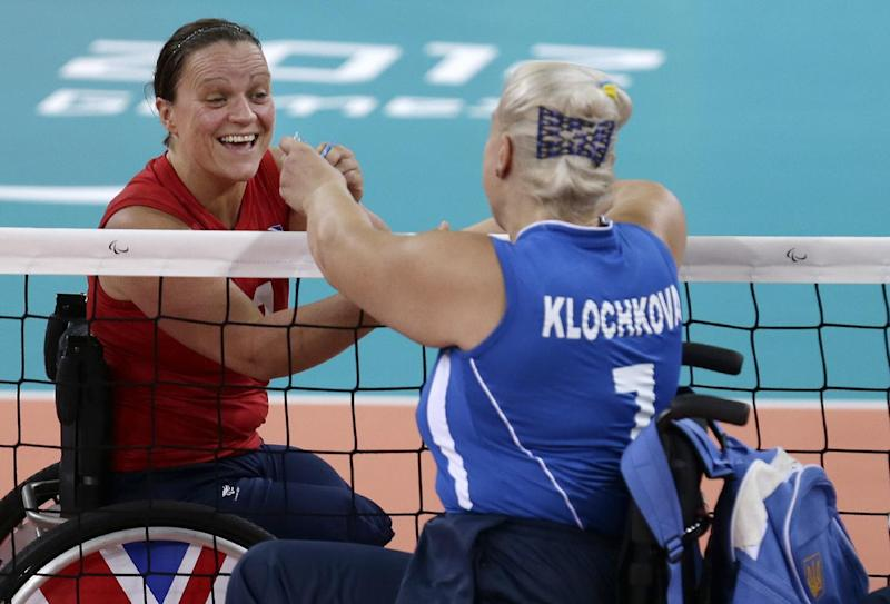 Martine Wright, left, of Britain  shakes hands with Larysa Klochkova left, of Ukraine, prior to their women' sitting volleyball match at the 2012 Paralympics games, Friday, Aug. 31, 2012, in London. On July 7, 2005, four suicide bombers detonated explosives on London's transit system, killing 52 commuters and the four attackers. Wright was among the injured on 7/7, losing both her legs. Seven years later, she's been transformed into an athlete, a Paralympian.(AP Photo/Alastair Grant)