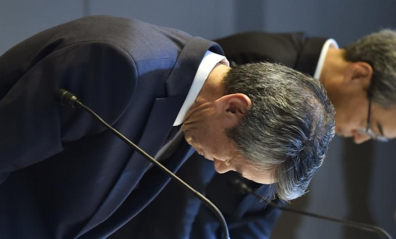 Former president of Toshiba, Hisao Tanaka (L) bows at the end of a press conference at the company's headquarters in Tokyo on July 21, 2015 (AFP Photo/Kazuhiro Nogi)