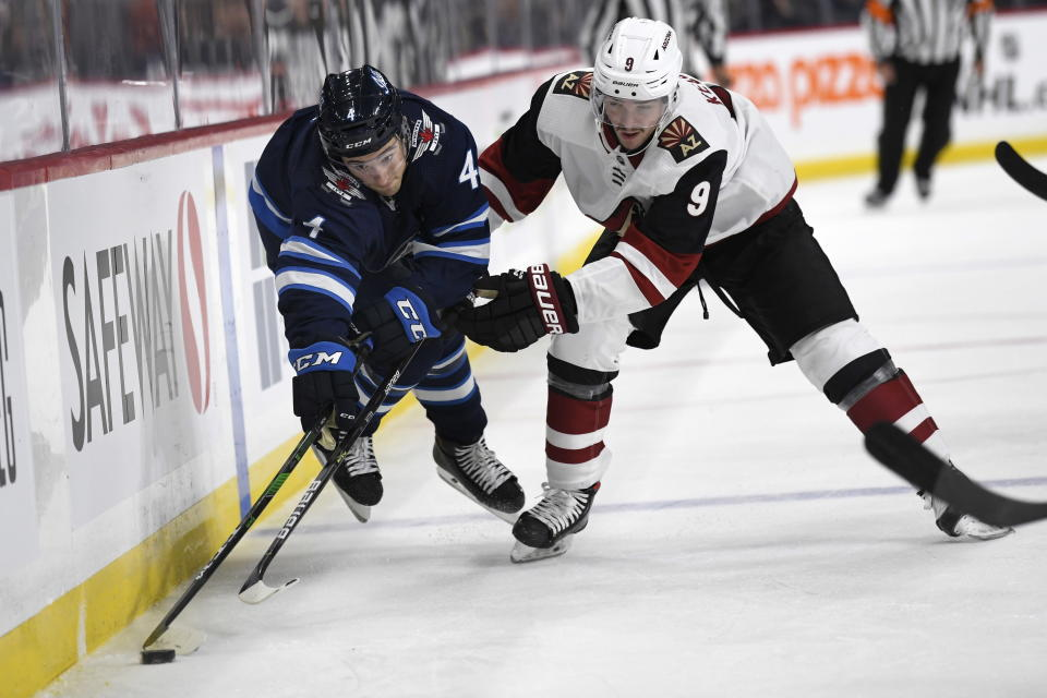 Winnipeg Jets' Neal Pionk (4) and Arizona Coyotes' Clayton Keller (9) chase the puck along the boards during the second period of an NHL hockey game Tuesday, Oct. 15, 2019, in Winnipeg, Manitoba. (Fred Greenslade/The Canadian Press via AP)