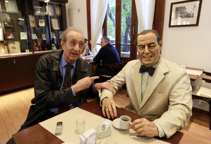 """Lorenzo Pepe, director of the Juan Peron institute, gestures as he sits next to a statue of former Argentine President Juan Peron at the """"Un cafe con Peron"""" (A coffee with Peron) restaurant in Buenos Aires May 8, 2011. REUTERS/Marcos Brindicci"""