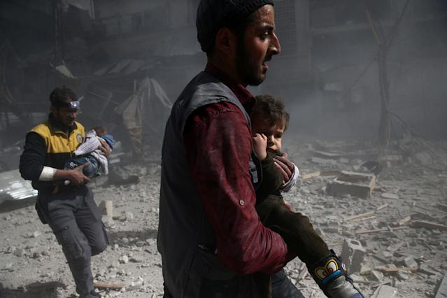 <p>A man holds a child after an airstrike in the besieged town of Douma in eastern Ghouta in Damascus, Syria, Feb. 7, 2018. (Photo: Bassam Khabieh/Reuters) </p>