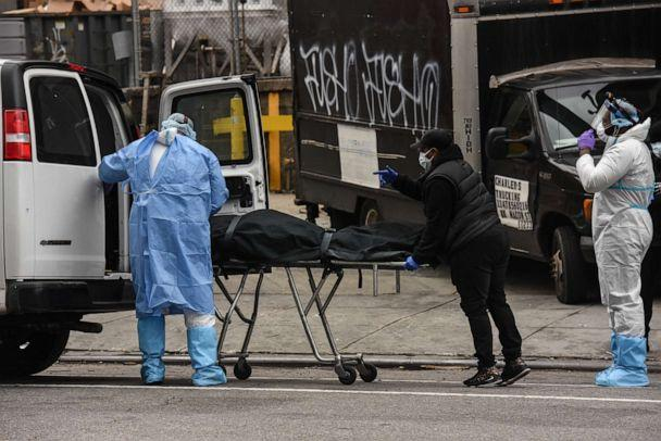 PHOTO: A funeral worker is assisted moving a deceased patient into a van at the Brooklyn Hospital Center on April 27, 2020, in New York. (Stephanie Keith/Getty Images)
