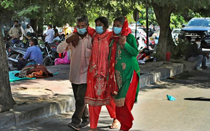 A woman is assisted to walk at a government- run hospital in Jammu, India - AP
