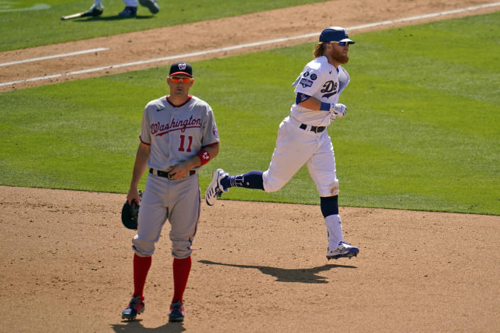 Los Angeles Dodgers' Justin Turner, right, rounds first base past Washington Nationals first baseman Ryan Zimmerman (11) after hitting a solo home run in the sixth inning of a baseball game, Friday, April 9, 2021, in Los Angeles. (AP Photo/Marcio Jose Sanchez)