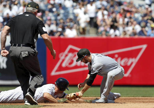 New York Yankees' Brett Gardner dives back safely avoiding the tag from Tampa Bay Rays second baseman Brandon Lowe on a pick off attempt as umpire Ted Barrett watches the play during the third inning of a baseball game, Saturday, May 18, 2019, in New York. (AP Photo/Jim McIsaac)