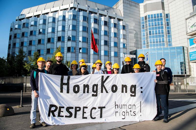 Pro Hong Kong supporters wear a patch on one eye and hold a banner calling for respect during a demonstration on August 23, 2019 outside the Chinese embassy in Berlin. - Ten weeks of demonstrations have plunged Hong Kong, the international finance hub, into crisis, with communist-ruled mainland China taking an increasingly hardline tone. Protesters, like in Hong Kong, wear symbolically eye patches, after a woman suffered an eye injury which demonstrators blamed on a bean-bag round fired by police. (Photo by Paul Zinken / dpa / AFP) / Germany OUT (Photo credit should read PAUL ZINKEN/AFP/Getty Images)