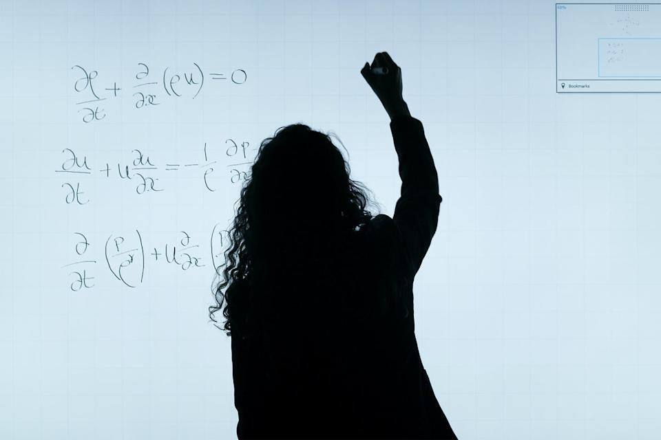 A woman is silhouetted in front of a white board as she writes mathematical equations on it.