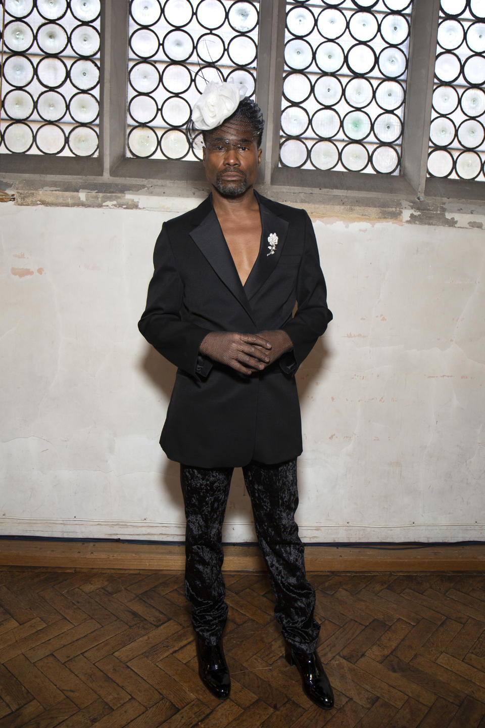 The actor attends the Sharon Wauchob SS20 show wearing a black tailored tuxedo and white fascinator [Photo: Getty Images]