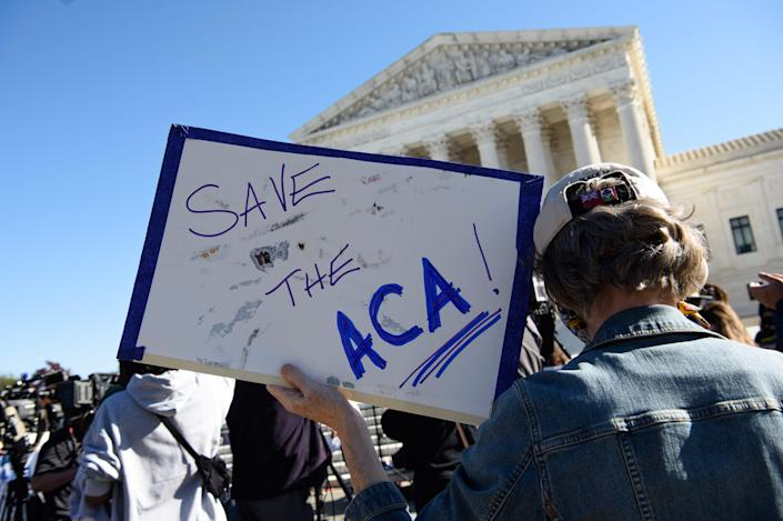 A protester holds a sign in front of the Supreme Court in Washington, D.C., on November 10, 2020, as the high court held oral argument in the long-brewing dispute over the constitutionality of the 2010 Affordable Care Act.