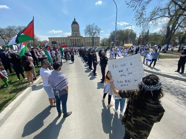 Pro-Palestinian and pro-Israeli demonstrators gathered in front of the Manitoba legislature in Winnipeg on Saturday. The groups were separated by more than a dozen police officers.