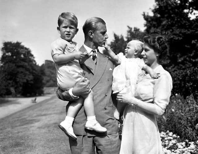 Princess Anne in the arms of Princess Elizabeth, with the Duke of Edinburgh, holding Prince Charles, in the grounds of Clarence House, their London residence