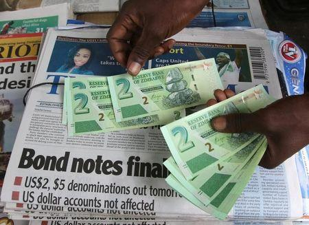 A street vendor poses with new bond notes in the capital Harare,